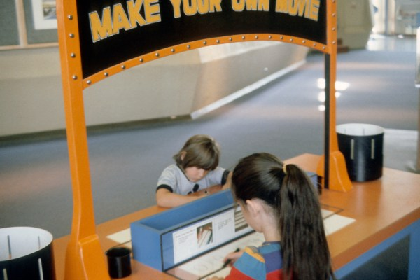 Two young girls sit facing each other at a 'Make Your Own Movie' exhibit, where they draw panels on a paper zootrope stripe.