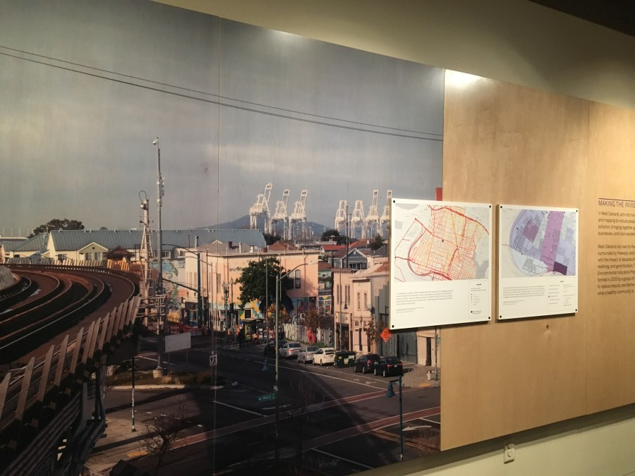 Wall-sized photo mural of West Oakland with two smaller maps hung beside it.