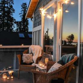 photo of balcony with string lights and candle lanterns