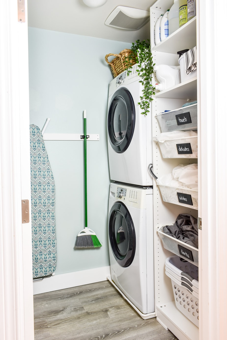 This small laundry room makeover on a budget makes the most of every square inch! It includes a stackable washer and dryer, sorting space, laundry basket storage, an ironing board, and space for detergent and cleaning supplies!