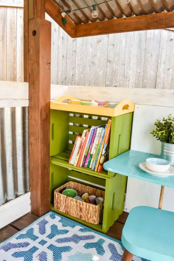 image of playhouse with bookshelves and mini dining table and chairs.