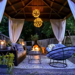 nightitme image of cedar gazebo from Yardistry with outdoor living room setup inside.