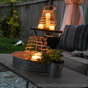 nighttime photo of outdoor living room with glowing candle lanterns