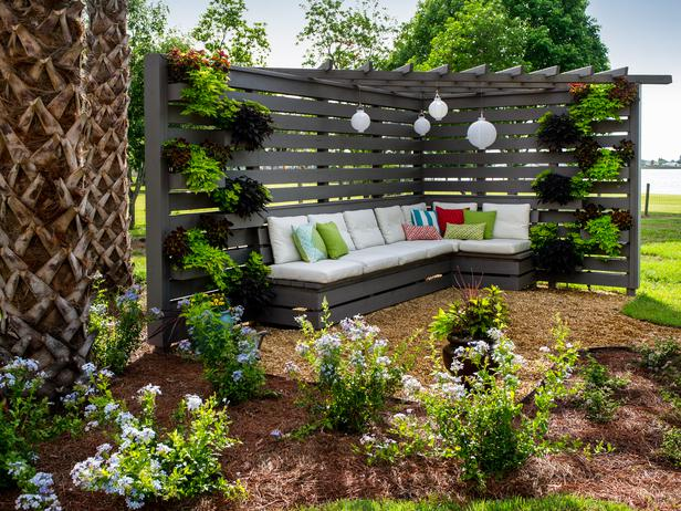 modern pergola patio shade idea with paper lanterns and outdoor sofa with cushions
