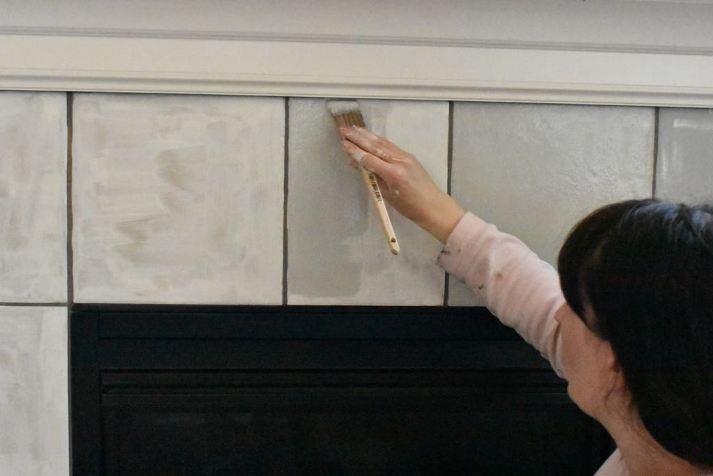 woman painting over primed fireplace tiles with light grey paint before stenciling