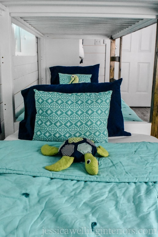 view of two bottom bunks with homemade stuffed sea turtle and seahorse on the beds