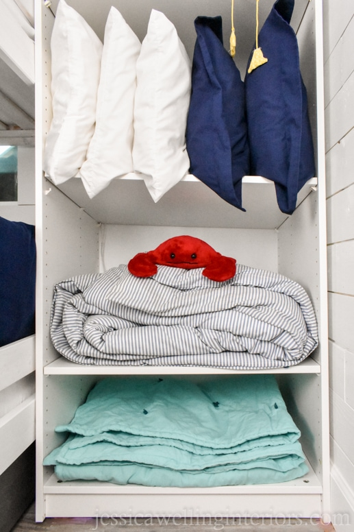 IKEA PAX wardrobe shelf unit used to store extra pillows and quilts in a beach house bunk room for kids with a stuffed crab