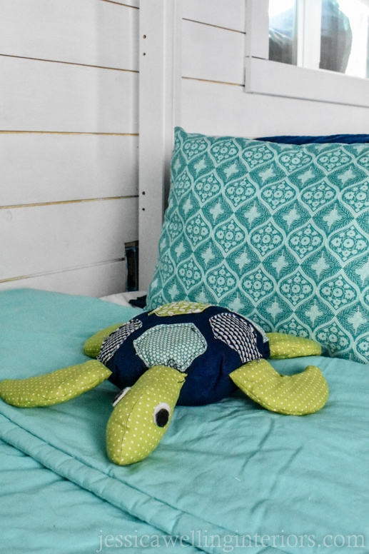 stuffed sea turtle on a child's bunk bed with aqua colored bedding