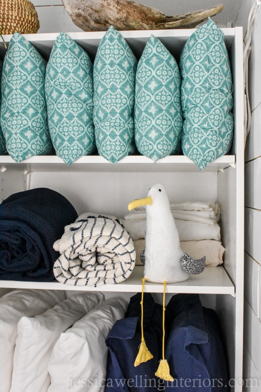 IKEA PAX wardrobe shelf hack used as an open linen closet in a beach house bunk room with a stuffed seagull