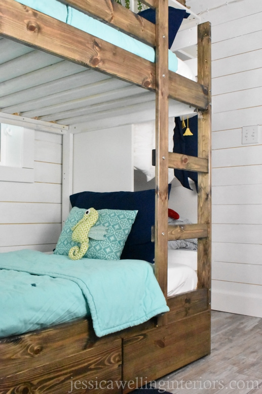 IKEA MYDAL bunk bed in a bunk room with aqua bedding and a stuffed seahorse on the pillow