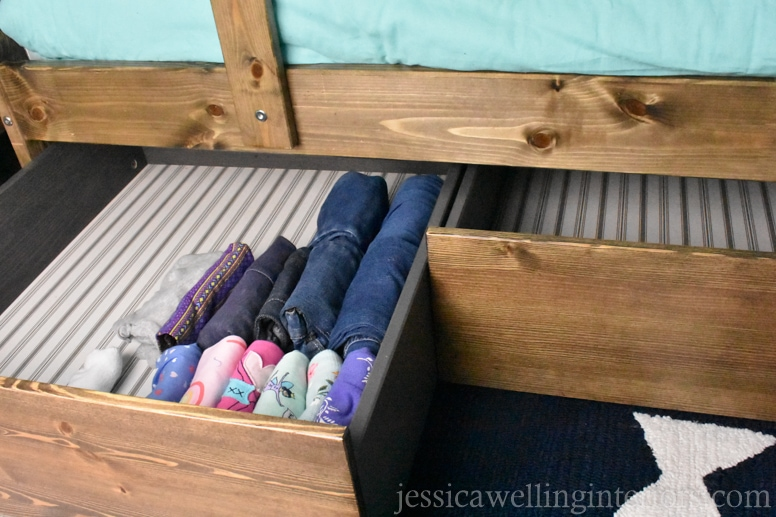 kids bunk room with IKEA hack under-bed storage drawer pulled out with child's clothing folded inside