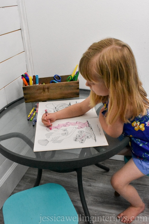 child coloring at a kids table