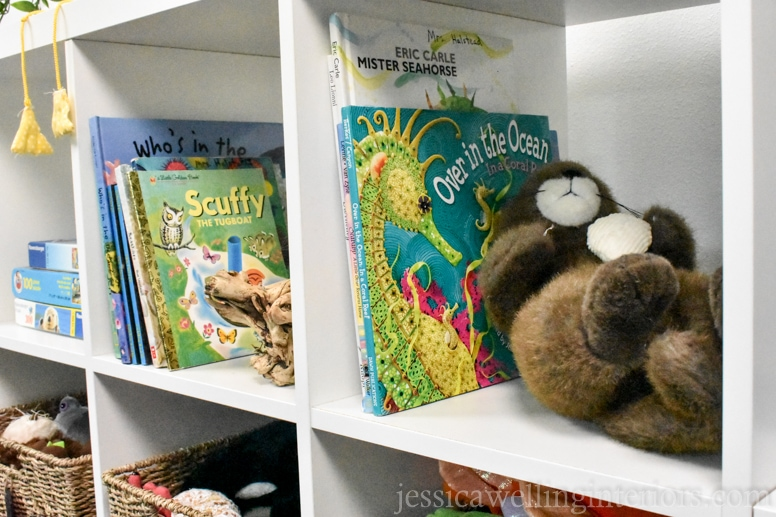 IKEA KALLAX bookshelf in white with ocean-themed children's books and a stuffed otter in a beach house bunk room