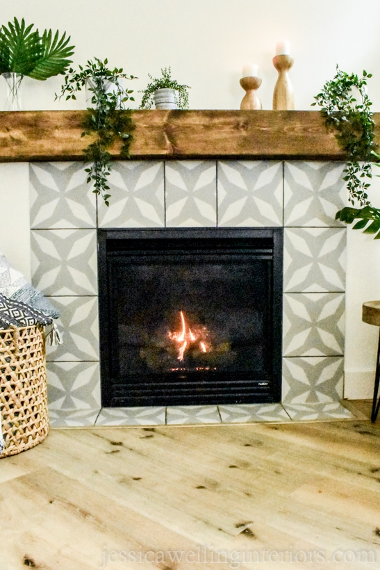 after photo of fireplace makeover- gas fireplace with faux painted cement tile in a grey and white morroccan pattern with a wood box mantel and indoor plants