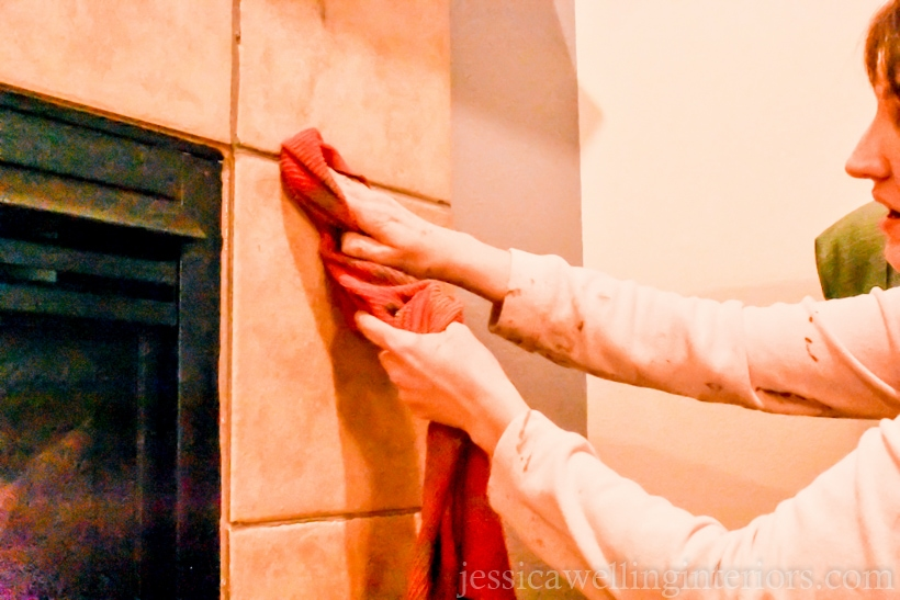 woman wiping tile grout around a fireplace with a damp rag to remove excess grout colorant
