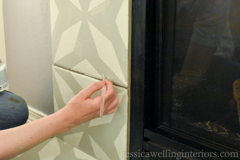 hand using a small angled artist's brush to touch up stencil pattern after removing the stencil to create a faux cement tile look around the fireplace