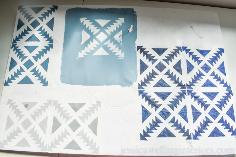 piece of white foam-core board with Aztec tile stencil painted on it in different shades of blue and grey