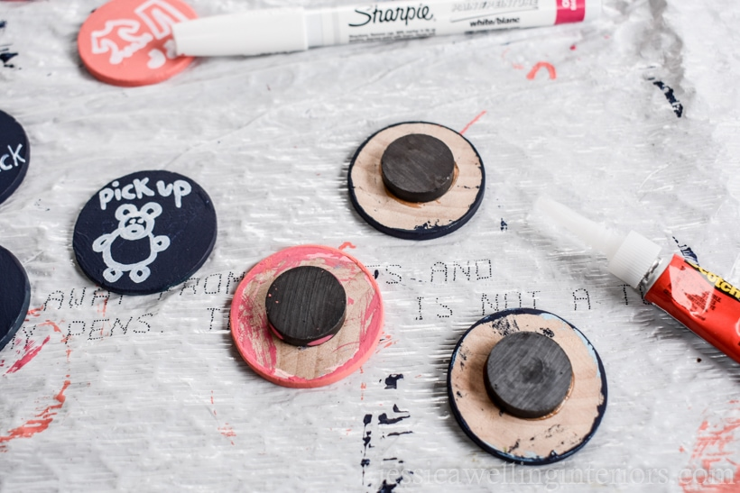 magnets glued to painted wood coins drying on a plastic trash bag