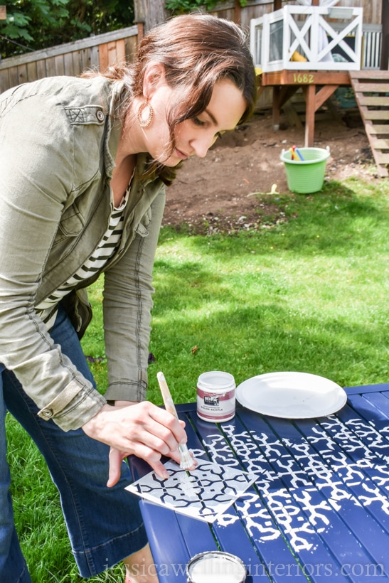 woman applying white paint to a patio table with stencil brush and stencil for painting