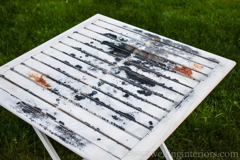 Old metal patio table with peeling paint and rust