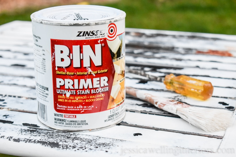 can of Zinsser BIN primer, paintbrush, and flatblade screwdriver sitting on old rusty patio table