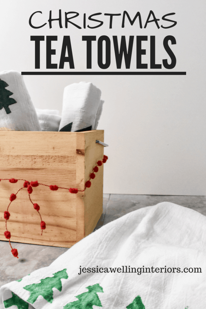 Christmas Tea Towels: wood box filled with rolled up stamped tea towels, and one tea towel stamped with Christmas trees laid on the counter next to it