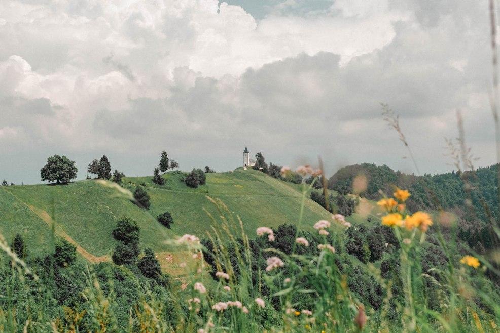 Fields and a hilltop church in Jamnik Slovenia