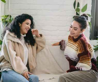 happy young women sitting on couch and talking