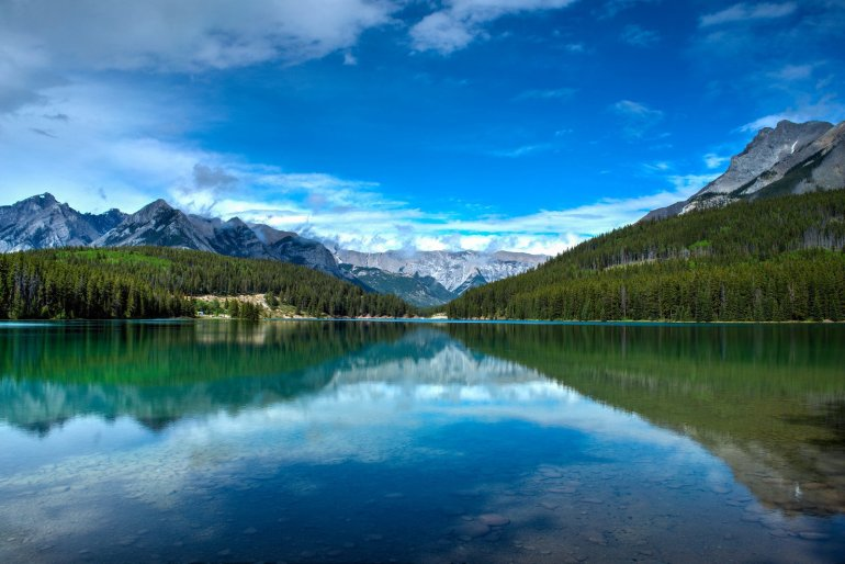 View of a clear reflective lake with mountain peaks in the distance in Banff National Park.