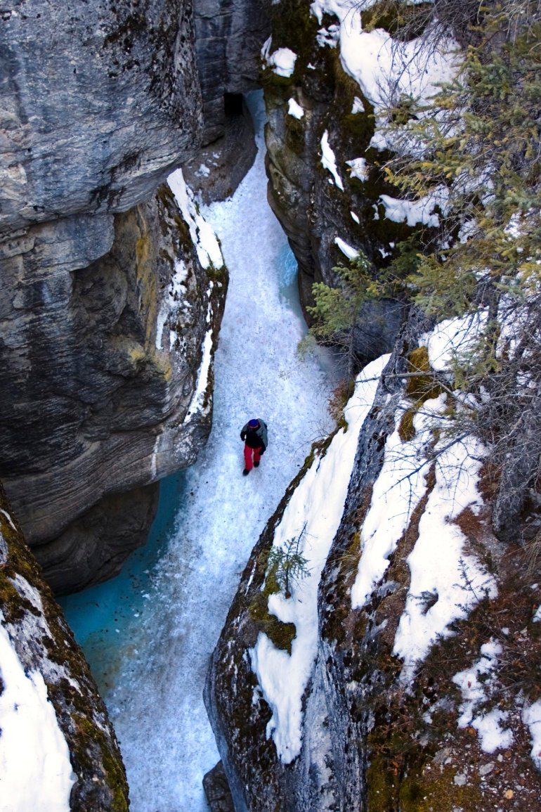 A top down view looking into a snowy canyon with a lone man hiking over the ice below.