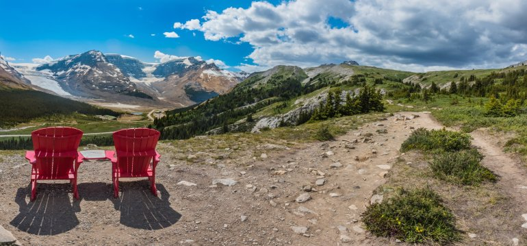 A pair of red chairs on the trail to Wilcox Pass in Jasper, Canada
