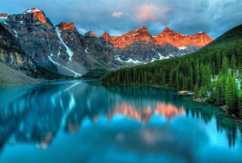 A view of Moraine Lake in the early morning. The seven peaks are glowing red.