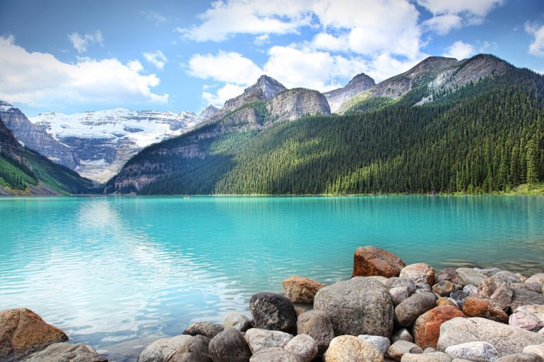 A turquoise Lake Louise sits in front of green trees and snowy mountains.