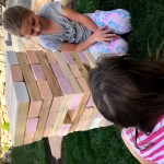 Life sized Jenga and two girls playing the game.