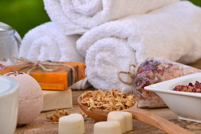 White towels, orange soaps, and white bath salts, spa items for a staycation spa day.