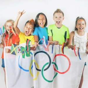 5 kids smiling and holding an Olympic flag and small flags from different countries.
