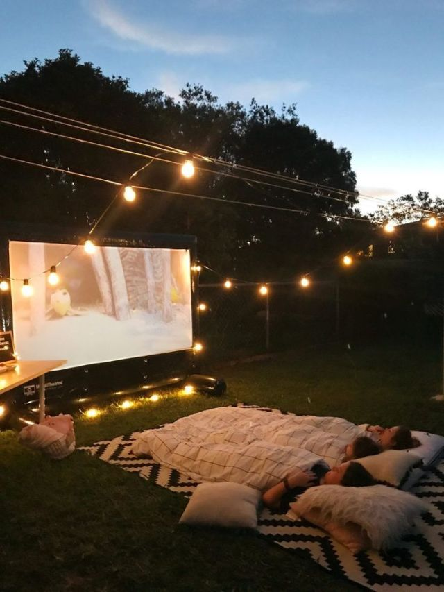 Movie screen outside with overhead landscaping lights and kids laying on a blanket watching the movie.