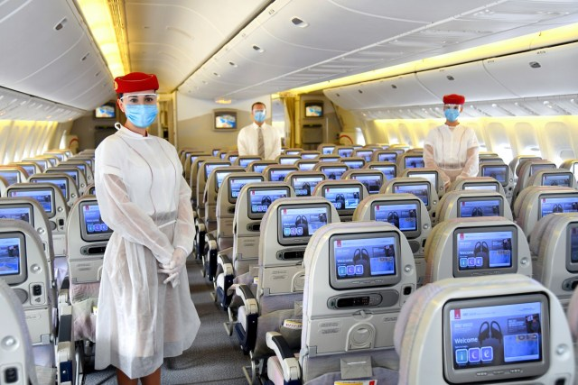 Emirates airplane and staff wearing masks and face shields for traveling after the coronavirus