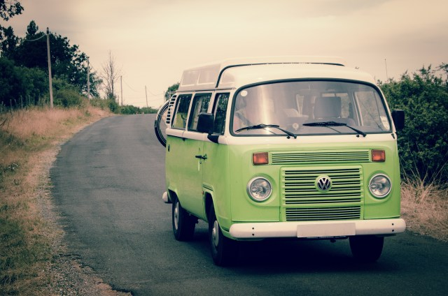 Green VW van driving on a country road for a road trip one of the safest ways to travel after Coronavirus