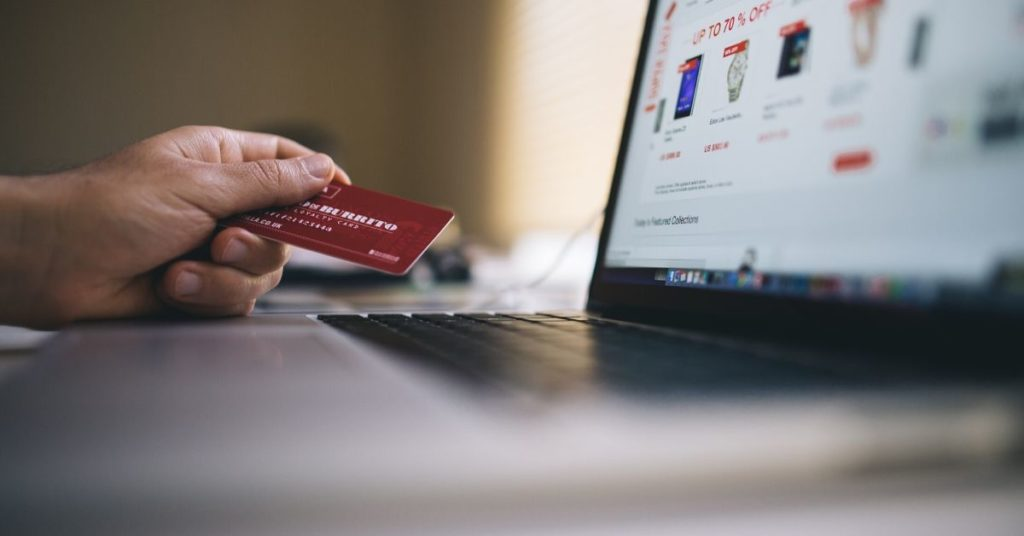 Picture of someone holding a debit card and looking at the computer