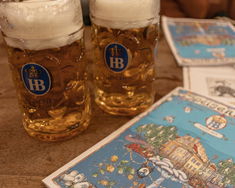 Eating a Hofbräuhaus Brewery must to have a meal with only one day in Munich. Picture of two pints of insanely large beers with menus.