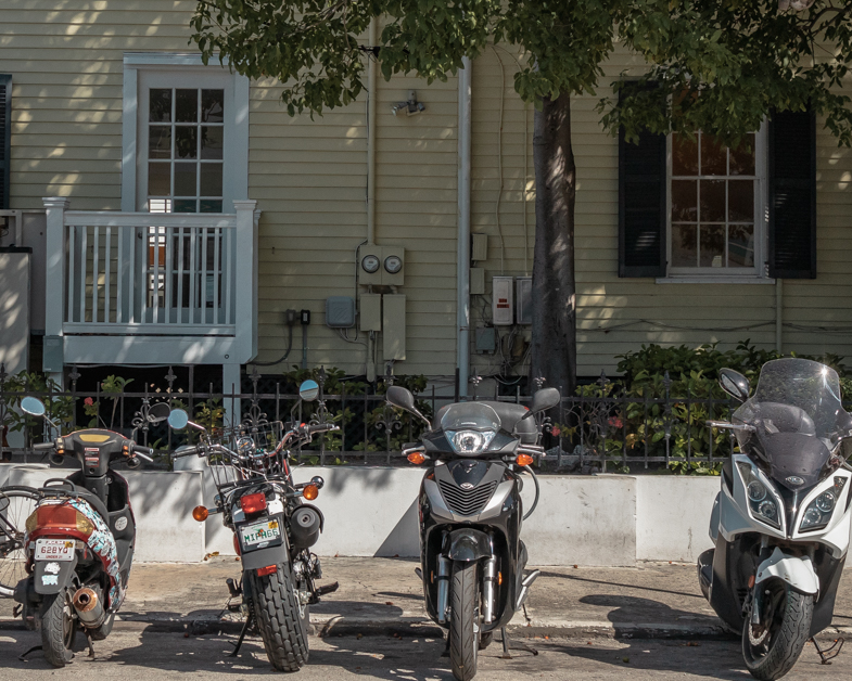 Motorcycles and scooters parked on the street in Key West.