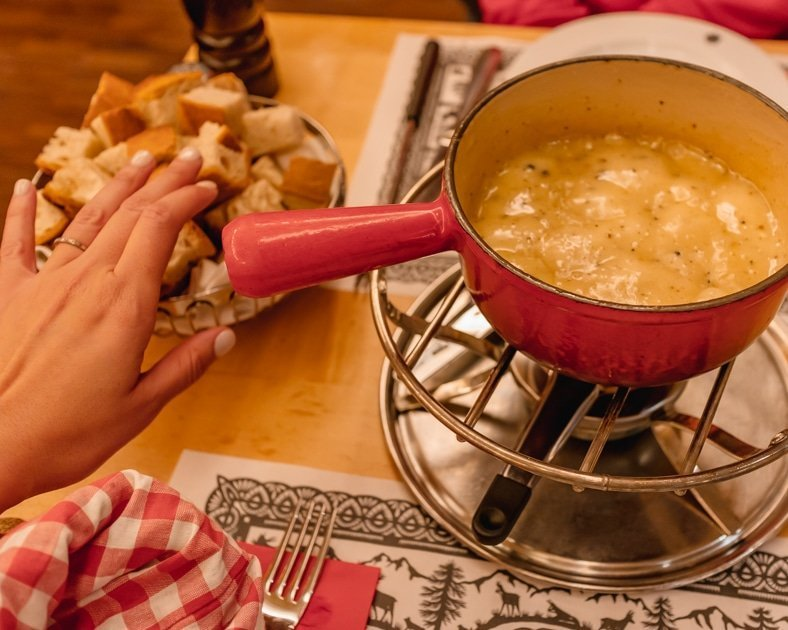 Me reaching for fondue at a restaurant in Zurich.