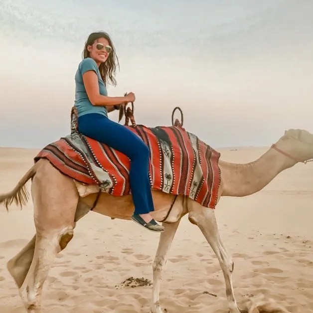 Riding a camel in the desert in Abu Dhabi one of the best solo female travel destinations