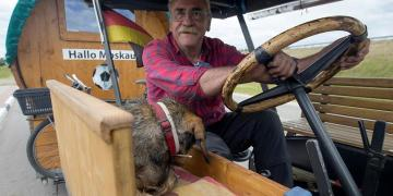 Soccer fan from Pforzheim, Germany, Hubert Wirth, 70, with his dog Hexe, drives his tractor with a trailer to attend the FIFA 2018 World Cup in Russia near the village of Yasen, Belarus June 7, 2018. REUTERS/Vasily Fedosenko