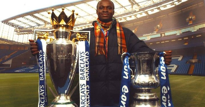 Akesse Sanza poses with Chelsea FC's FA Cup and Premier League trophies