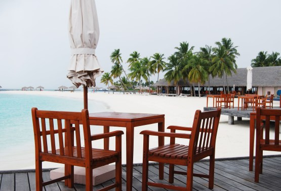 outdoor restaurant tables looking out at the beach maldives