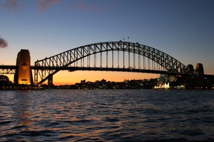 Sun setting behind Sydney Harbour Bridge in Sydney, Australia
