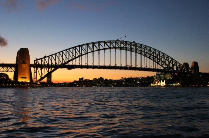 Sun setting behind Sydney Harbour Bridge in Sydney, Australia