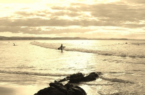 Surfer with board walks into water at dusk in Coolangatta, Gold Coast, Australia